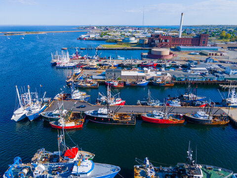 New Bedford harbor aerial view with fishing boats docked at piers near historic downtown of New Bedford, Massachusetts MA, USA.