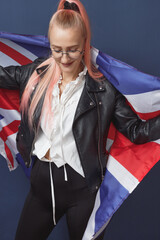 Young woman expat in eyeglasses with great britain flag. Studio shot. English language hipster...