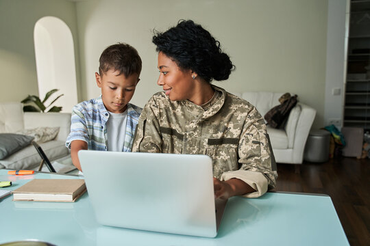 Black mother and son using laptop at table