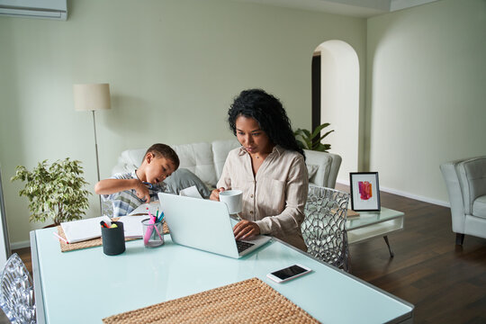 Black mother using laptop and child crafting