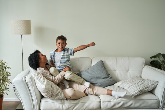 Black mother and her son resting on couch