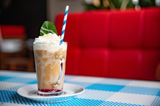 Iced caramel latte coffee in a tall glass with white chocolate syrup, whipped cream and mint leaf.