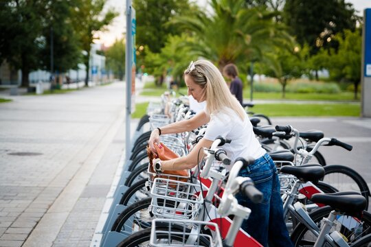 Blonde woman uses the bike in the city. Concept of healthy lifestyle in the city.