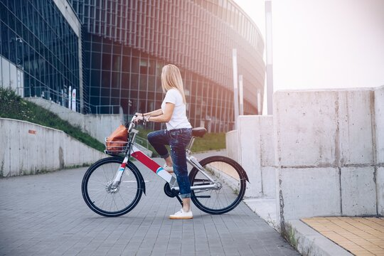Young woman with modern city bike. Clean sustainable urban transportation.