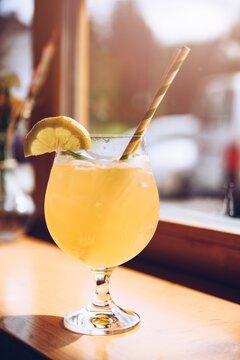Refreshing lemonade glass with ice cubes and fresh lemon.