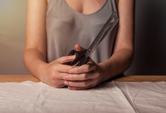 Seamstress hands holding professional tailor scissors in hands closeup over natural pastel cloth.