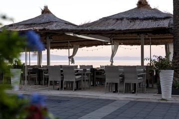 Obraz Chorwacka poranna plaża, stoliki z restauracji przy przy plaży w miejscowości Podgora. - fototapety do salonu