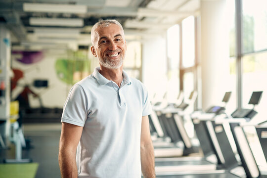 Portrait of happy mature athlete during sports training at gym.