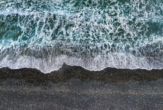 Stormy green waves with white sea foam breaking on dark sandy beach, view from directly above