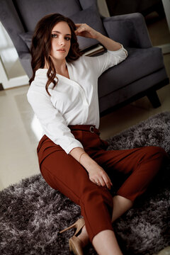 A young beautiful girl with a beautiful hairstyle and makeup in a white blouse and red trousers sitting on the floor, leaning on a chair. Portrait of a model in office style clothes.