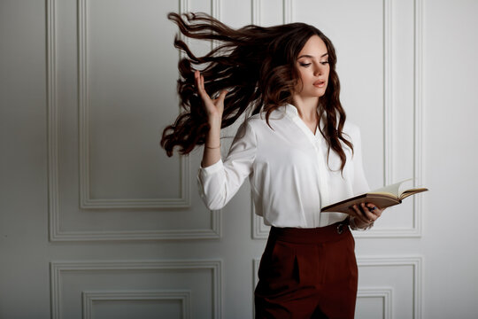 A beautiful young girl reading a book and throwing long wavy hair up. Model in a white blouse and red trousers in office style clothes. Space for text.