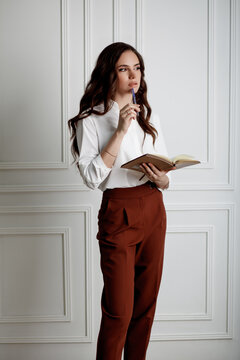 A beautiful young girl with long wavy hair reading a book thoughtfully. Model in a white blouse and red trousers in office style clothes.