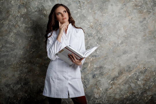 Portrait of a beautiful girl with long wavy hair. A female doctor in a white medical coat reading a large book thoughtfully. Space for text.