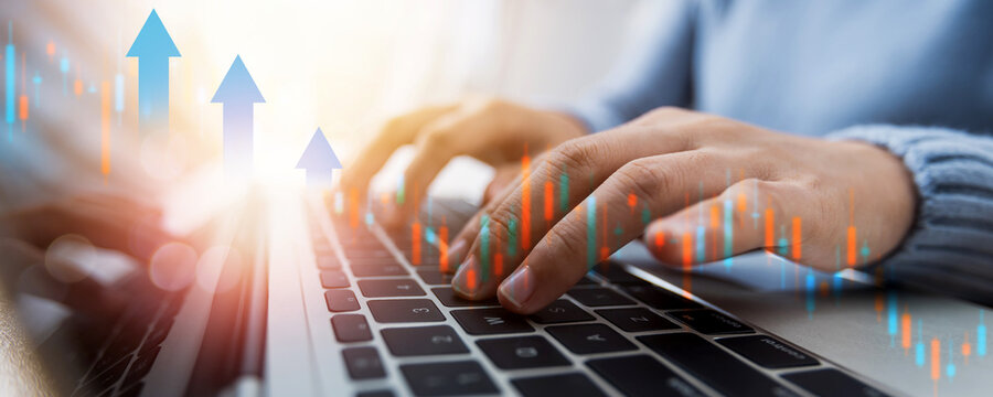 Stock market and financial cryptocurrency trade concept, close up hand of woman freelance working, trading and typing on laptop with graph at home