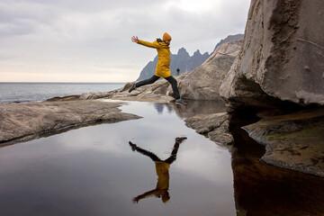 Woman, having fun in Tungeneset, Senja, Norway, jumping over big puddle, making reflection in water