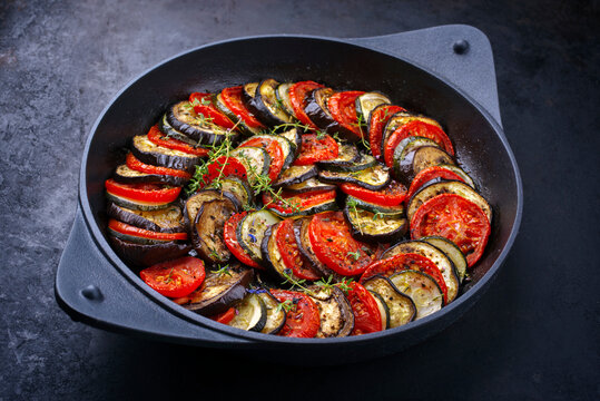 Modern style traditional French ratatouille with tomatoes, eggplant and zucchini served as close-up in a rustic cast-iron skillet