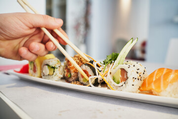 Unrecognizable person taking sushi rollo from plate served on table