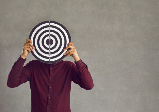Young casual african american man holding dart board hiding face standing over grey studio background. Business goal and competition challenge, target aiming to succeed, strategic planning concept