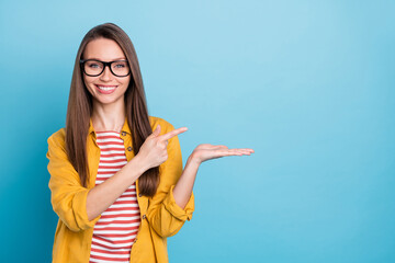 Photo of young woman happy positive smile point finger product promo advert choice sale isolated over blue color background