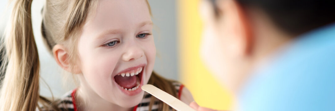 Pediatrician doctor examining throat of little girl with spatula