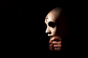Fototapeta Side image of mask in hand with black background. Side view of high contrast photograph. halloween concept with copyspace. obraz