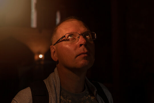 Mature man in eyeglasses looking up to light from heaven. Spiritual insight concept.