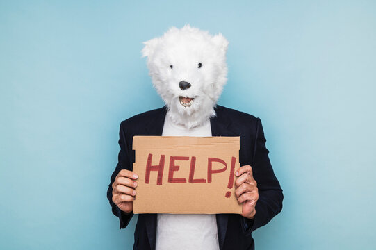 Man in a polar bear mask holding a sign that says HELP. Concept save the planet.