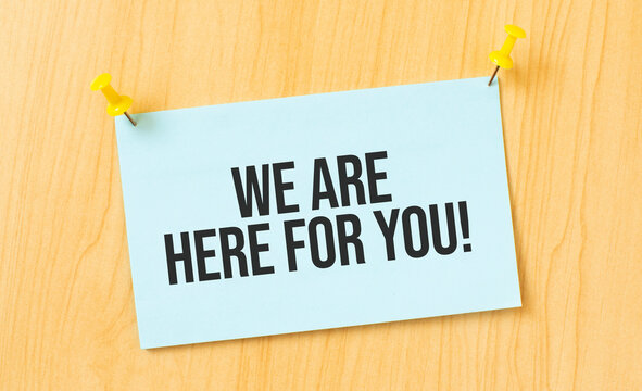 We are here for you sign written on sticky note pinned on wooden wall