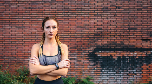 Sportswoman with crossed arms posing in front of a brick wall