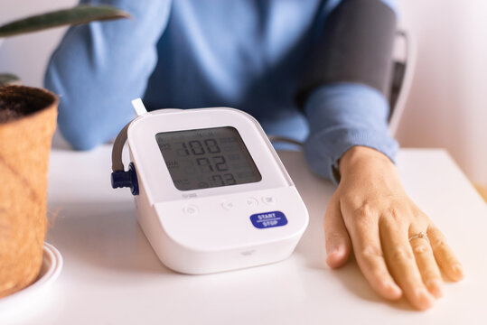 Patient women using blood pressure and heart rate monitor for yourself at home