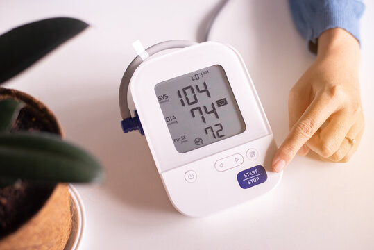 Patient woman using blood pressure and heart rate monitor for yourself at home