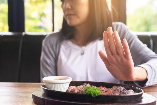 Hands woman refusing beef steak in restaurant,No meal,Vegetarian and vegan concept