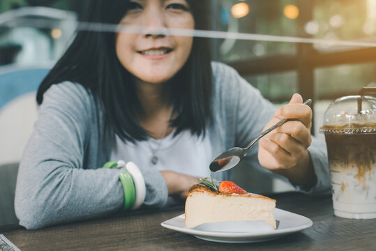 Woman hands holding spoon and eating cake with strawberry on top at a cafe