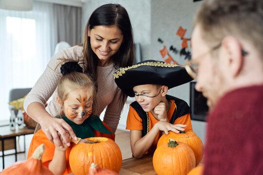 Family preparing pumpkins for Halloween