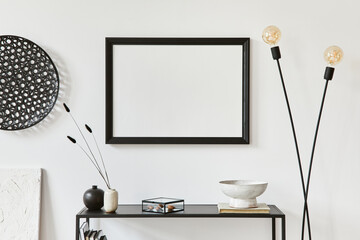 Minimalistic stylish composition of creative room interior design with mock up poster frame, metal shelf, industrial lamp and personal accesories. Black and white concept. Template.