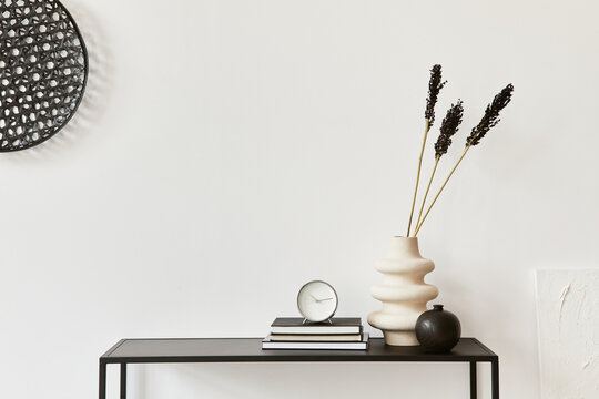 Minimalistic stylish composition of creative room interior design with copy space, metal shelf, plants and personal accesories. Black and white concept. Template.