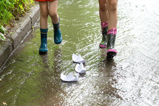 Kids are playing with paper boats in a water stream after rain on a city sidewalk