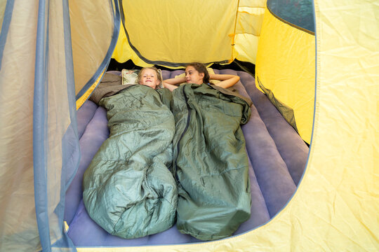 Two happy young girls lying in sleeping bags in a tent