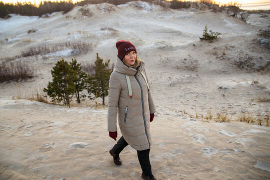 Woman walking on the Ssand dunes with pine forest over sea in the winter at White sea, Arkhangelsk