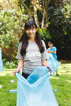 Portrait of smiling asian daughter putting rubbish in refuse sacks with family in the countryside