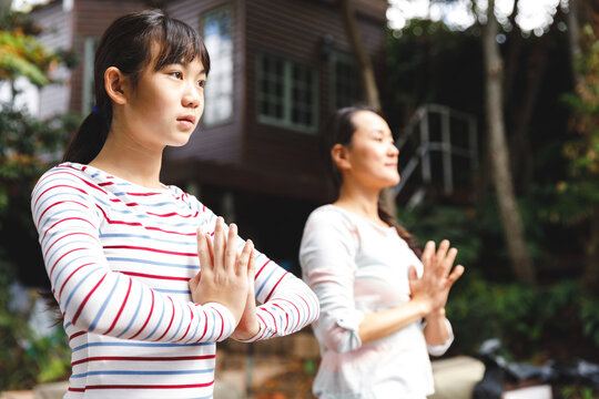 Asian mother and daughter exercising outdoors and practicing tai chi