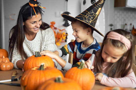 Mom with kids preparing pumpkins for Halloween