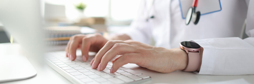 Doctor sitting at table and typing on computer keyboard closeup