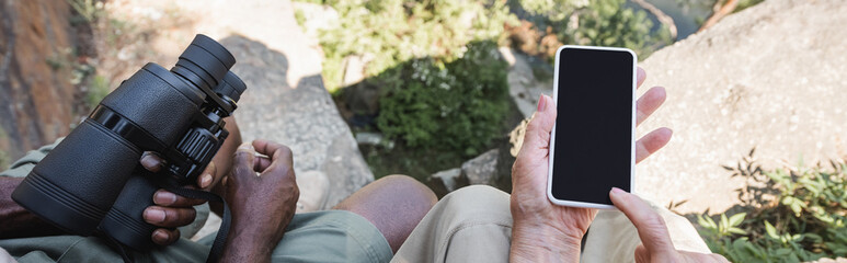 Top view of interracial couple holding smartphone and binoculars on stones, banner.