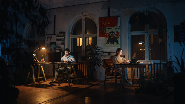 Two Stylish Employees Working on Computers in Creative Agency in Loft Office. Colleagues Answer Emails and Manage Marketing Projects. Dark Renovated Space in Evening with Plants and Artistic Posters.