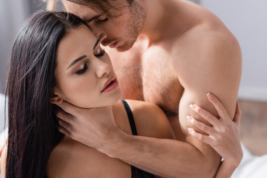 passionate man touching neck of seductive woman in black underwear.