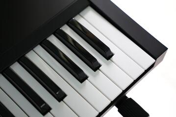 A black midi keyboard with black and white keys in a studio