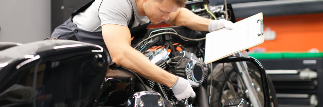 Male mechanic diagnoses parts on motorcycle at service center