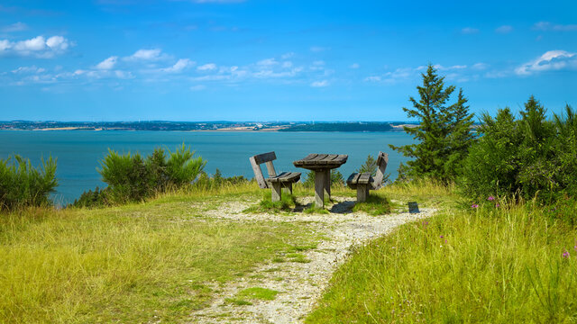 beautiful coastline with picnic table and benches on a sunny summer day