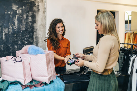 Beautiful young blond woman paying her new clothes buyed in expensive boutique with credit card.